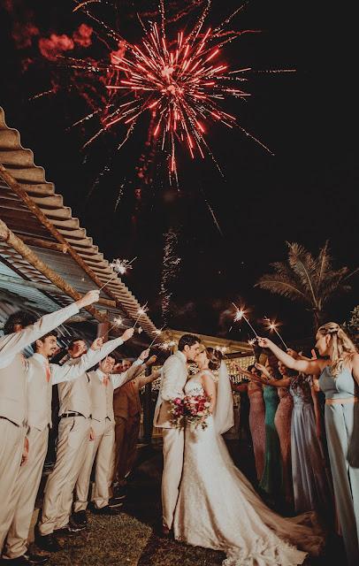 Novios besándose mientras los invitados agitan bengalas y hay fuegos artificiales