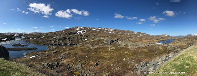 Blue sky, lakes, clouds and rests of snow on the Hardangervidda Mountain Plateau in Norway