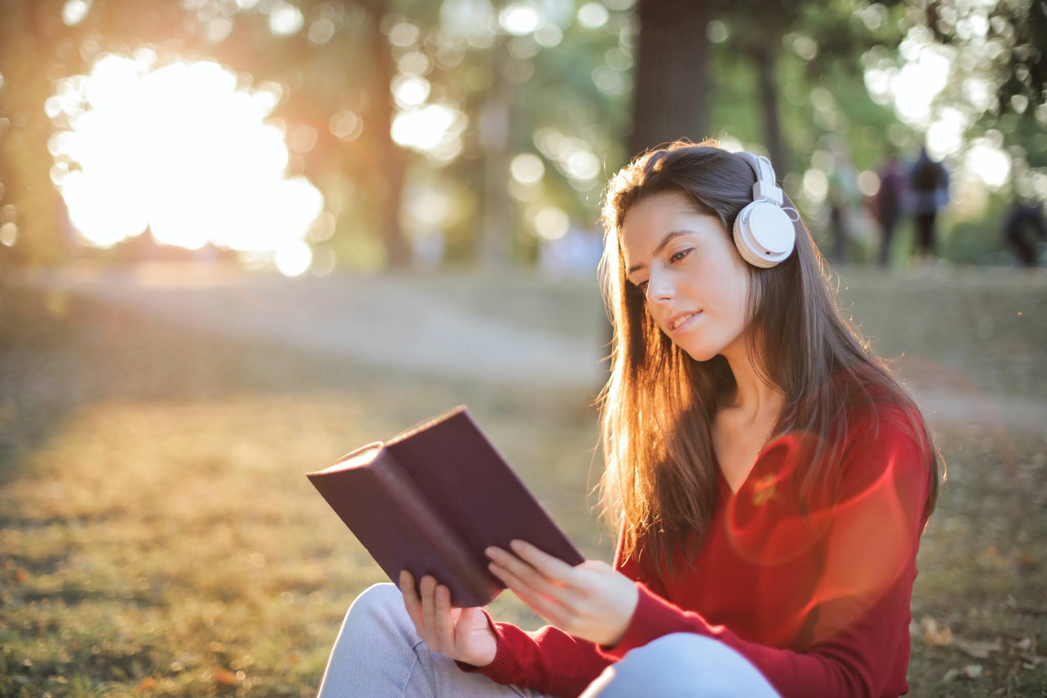 Girl wearing headphones reading a book. Photo by Andrea Piacquadio from Pexels