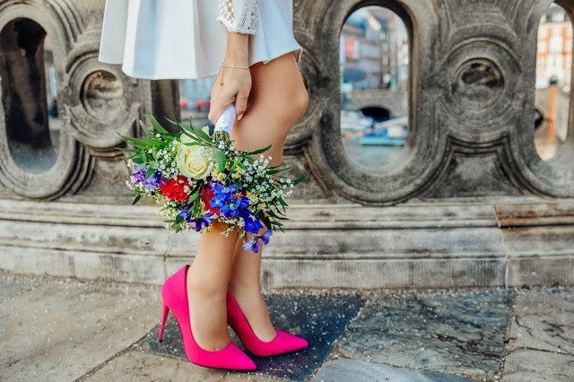 woman in pink shoes holding bouquet