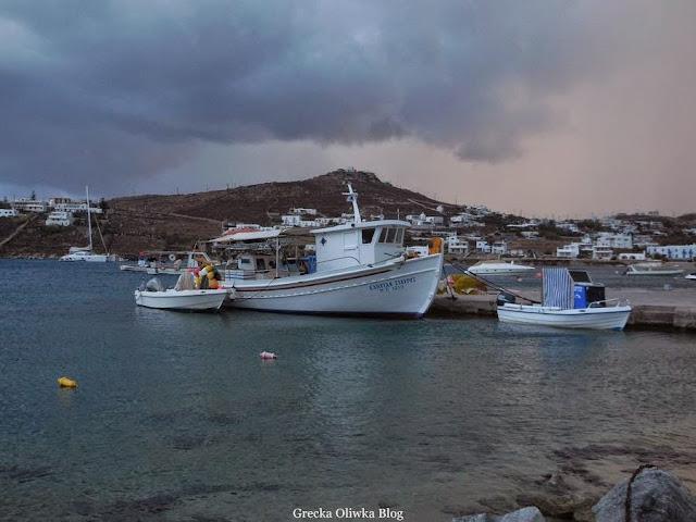 Białe łódki rybacie na tle pociemniałego egejskiego morza i nieba Mykonos Grecja przed burzą