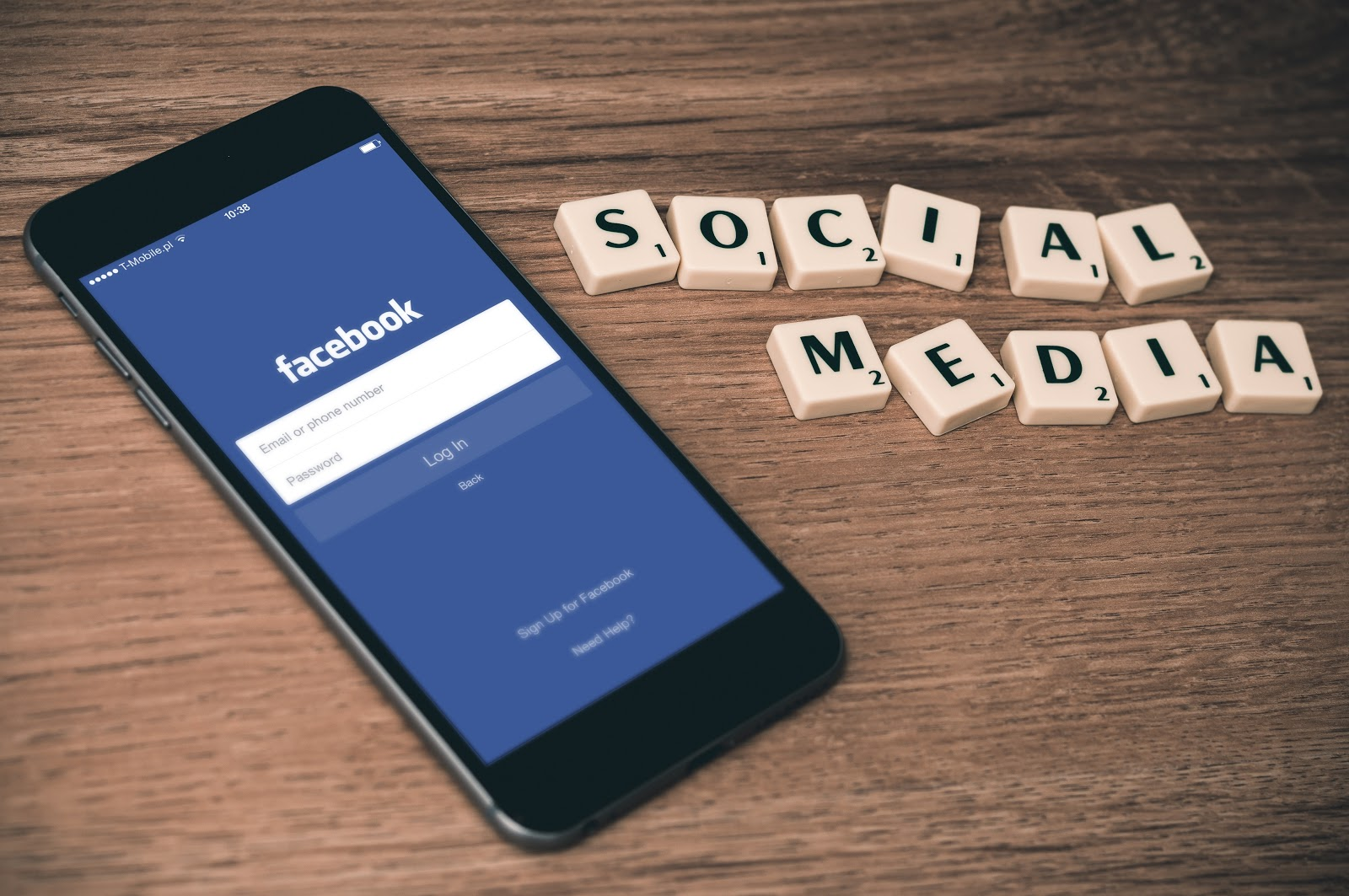 Facebookのログイン画面を映したスマホと「SOCIAL MEDIA」の文字のブロック