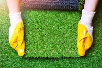 Piece of artificial grass being held by gloved hands