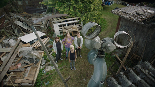Four children look up at the large sculpture made out of junk that they made