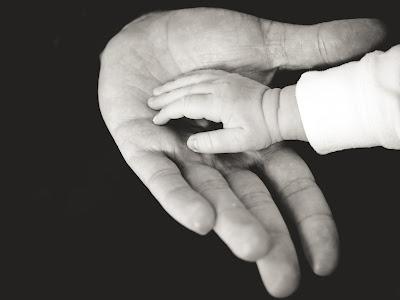 صورة ليد أب وابنته أو ابنه يمسكان بأيدي بعضهما البعض