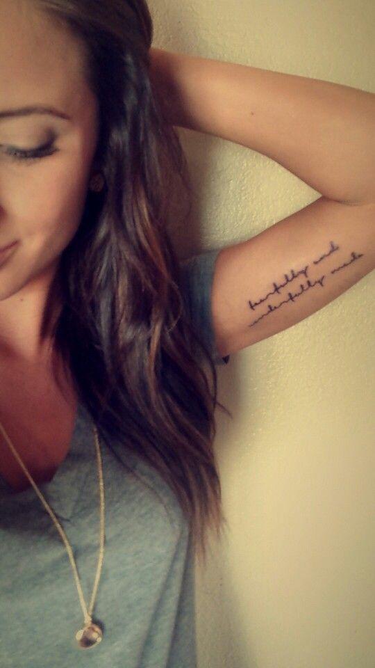 chica sonriendo con tatuaje de frase en el brazo