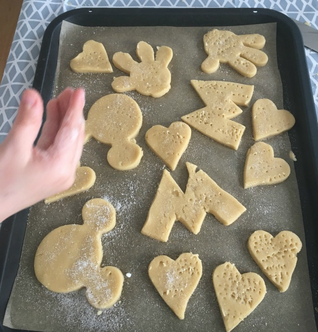 cookies-on-baking-tray-shapes-are-mickey-Mouse-head-hand-andletter-M-also-a-few-hearts-pricked-with-a-fork-and-lots-of-sugar-sprinkled-on-one