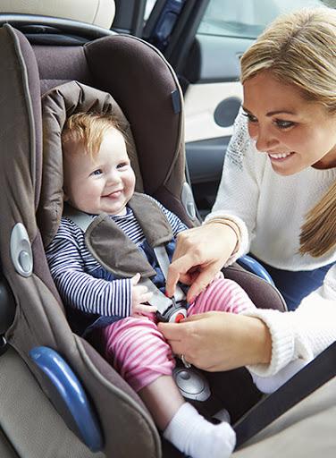 Woman buckling baby into car