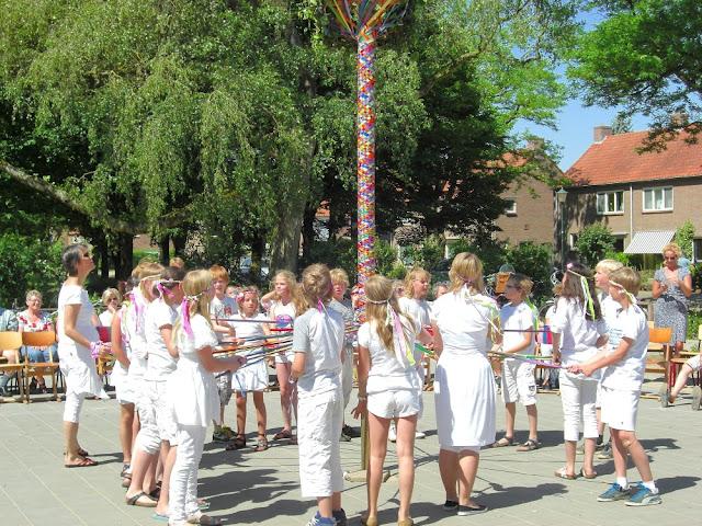 Leerlingen dansen rond de meiboom op het schoolplein