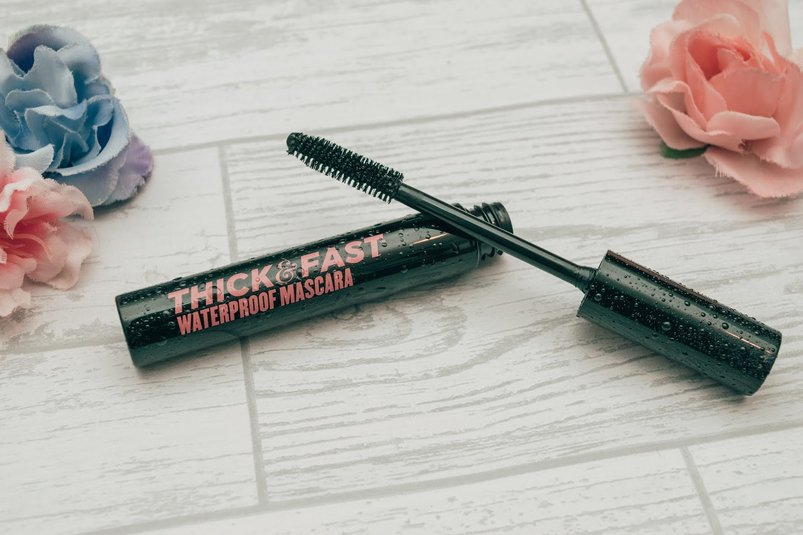 An open mascara tube with the wand balancing on the tube.