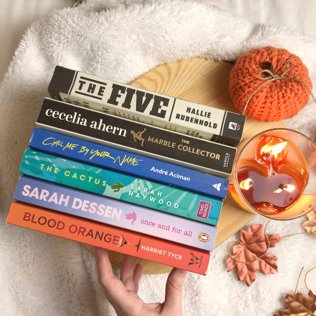 6 books in a stack with their spines facing up next to fake autumn leaves