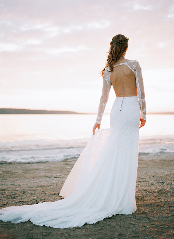 This sexy open back wedding dress has a floaty skirt and long sheer sleeves. It's perfect as a destination wedding dress. It's one of many affordable wedding dresses from She Wore Flowers.