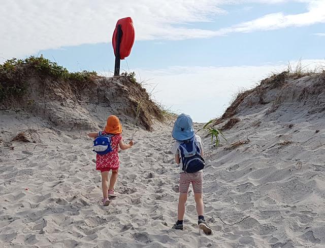 Warum unsere Kinder ihre Rucksäcke selbst tragen (+ Rucksack-Tipps). Bei diesem Ausflug an den Strand können unsere Kinder ihr Sandspielzeug und ihr Proviant in ihren Rucksäcken leicht selber tragen.