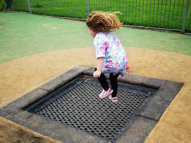 Image of a sunken trampoline in Graves Park Play area. A young girl is mid-jump suspended in the air above the trampoline.