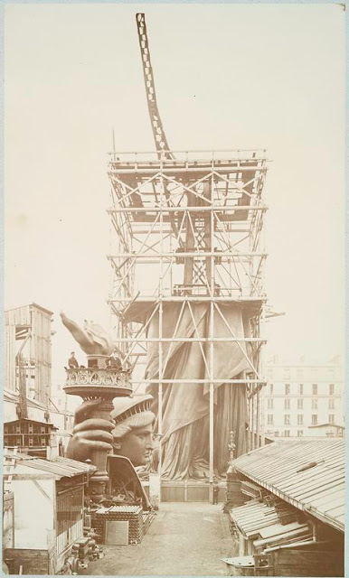 [Assemblage of the Statue of Liberty in Paris, showing the bottom half of the statue erect under scaffolding, the head and torch at its feet.]. Fernique, Albert -- Photographer. 1883. Source: Album de la construction de la Statue de la Liberte. Repository: The New York Public Library. Photography Collection, Miriam and Ira D. Wallach Division of Art, Prints and Photographs.
