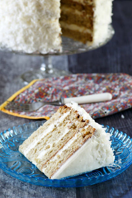 slice of layered banana cake with white frosting and coconut with remaining cake in background