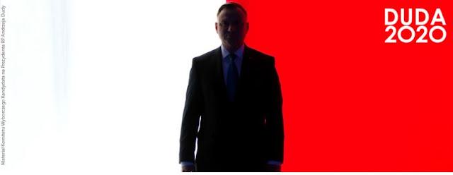 Andzej Duda z zacienioną twarzą na tle polskiej flagi