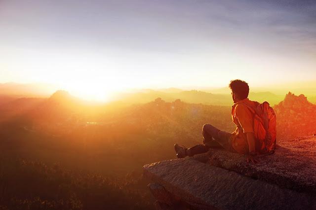 homem sentado na pedra olhando o pôr do sol