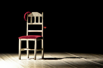 An empty chair sits on an otherwise empty stage in an empty theater.