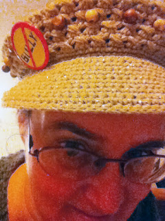 Close-up of Cynthia M. Parkhill, wearing a yellow-crocheted hat with a 'No Bully' pin, the word 'Bully' in black letters on yellow with a red circle and red-line diagonal strike-through