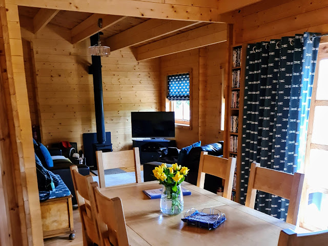 Image of other side of living accommodation. View of solid wood dining table that seats six. Open plan living room with log burner, two leather sofas, beanbag and matching blue dragonfly patterned soft furnishings