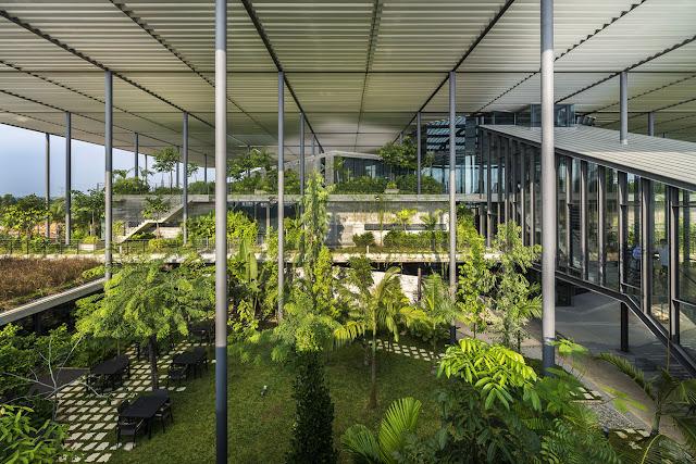 hall de fabrica en el bosque con vegetación interior y techo de persiana alto