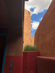 View of adobe wall and blue sky.