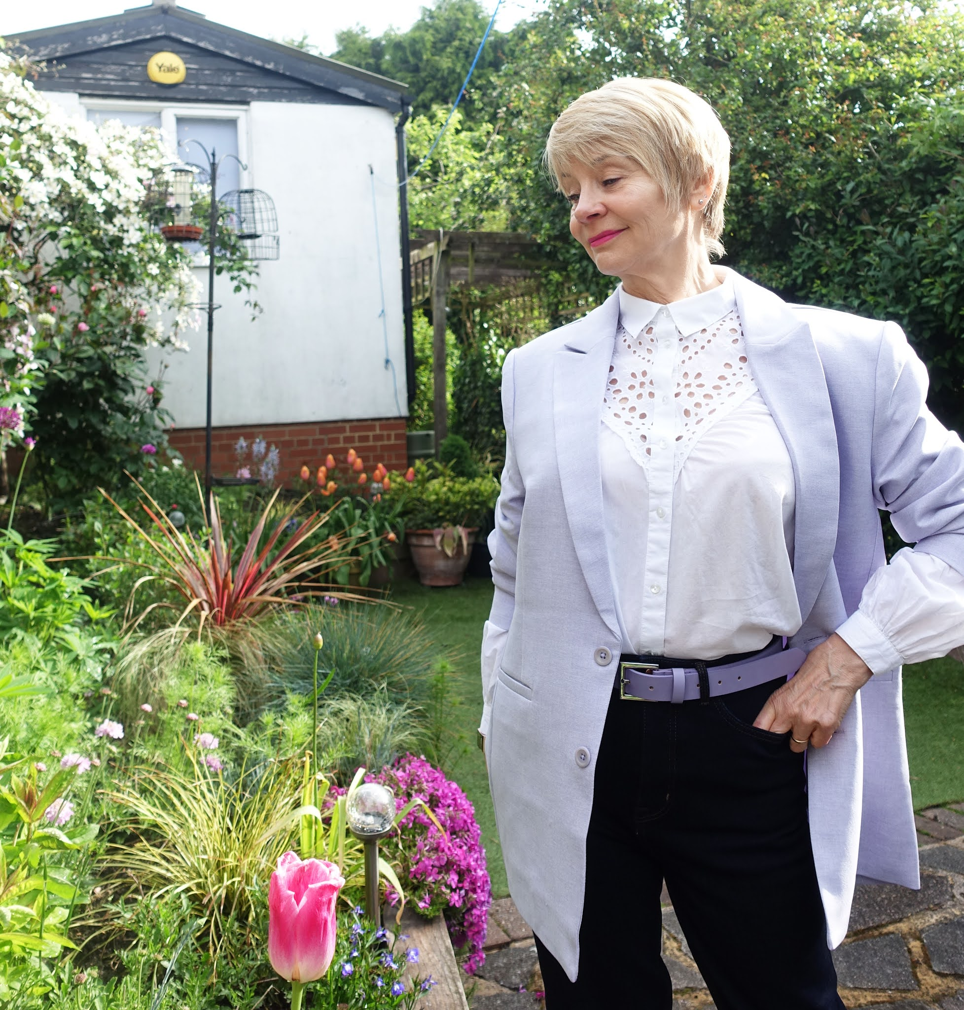Over 50s blogger Gail Hanlon in casual chic outfit of oversized lilac blazer, shaping jeans and white broderie blouse with trainers