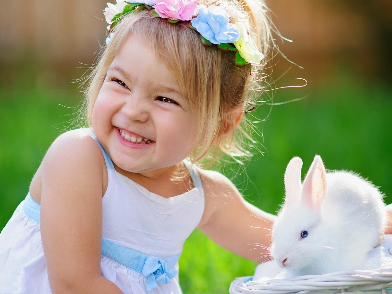 Gambar bayi perempuan cantik tersenyum dan bermain dengan kelinci