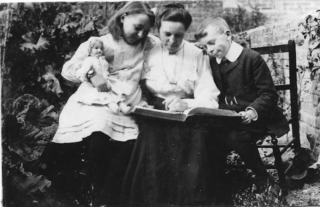 Seated family group, reading a book on the mother's knee