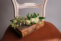 bible sitting on wood round table, white roses on top of it and a white chair in the back