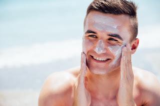 homem bonito usando protetor solar