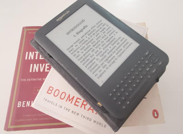 Kindle eReader sitting on top of several books