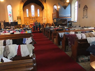 Pews at St Paul's festooned with clothes. Toys, furniture and bric-a-brac was across the front