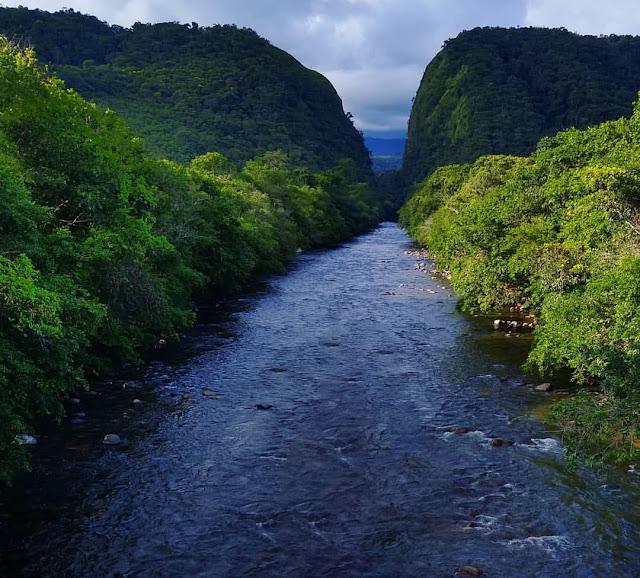 río cristalino con dos montañas verdes al fondo