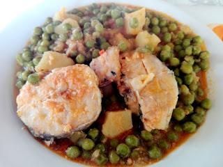 Merluza guisada con patatas y guisantes.