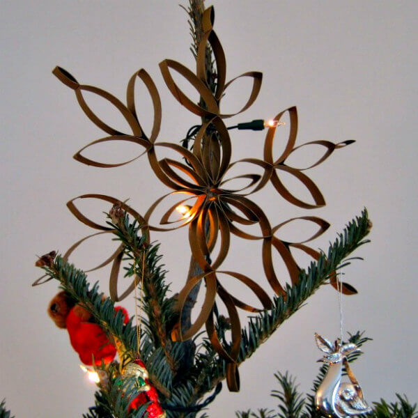 snowflake tree topper on lighted Christmas tree