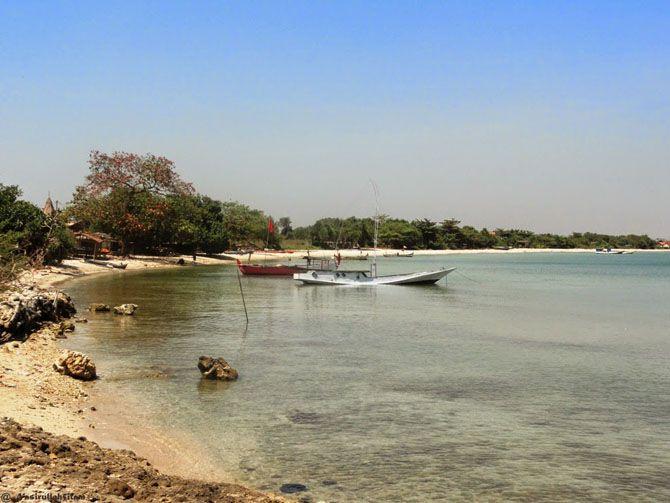 Hamparan pasir di pantai ombak mati dan beberapa kapal tertambat