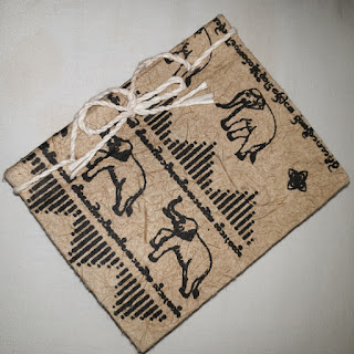 A handmade notebook with handmade paper, elephant images on its hardboard cover