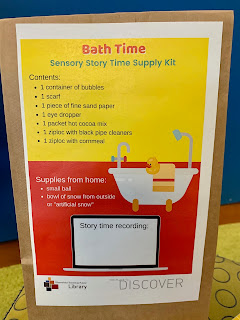 Closeup of small brown paper bag with Bath Time Sensory Story Time Supply Kit label attached. A list of supplies and images of a bathtub and laptop are on the label.