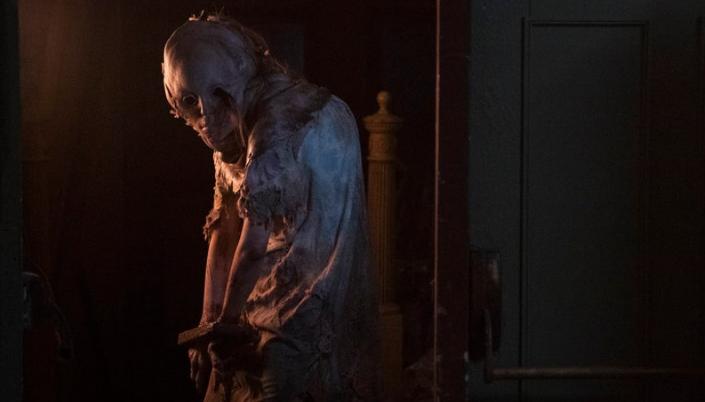 Imagem: uma criatura monstruosa com um rosto enorme, inchado e pálido, com olhos vazios, apenas órbitas, a cabeça crescendo no corpo de uma garota jovem num vestido algemada.