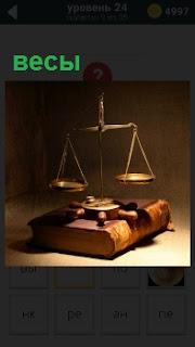 На картинке изображение весов, стоящих на толстой книге, очень похожей на библию