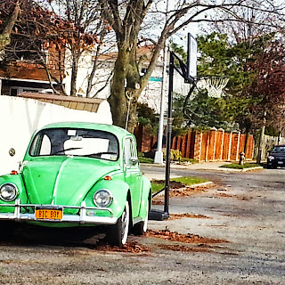 A green Volkswagen Bug parked on a side street in Staten Island