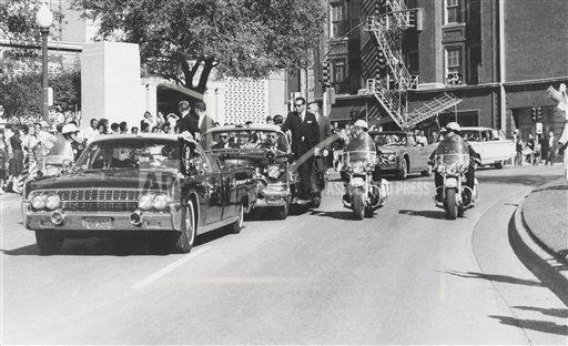 Kennedys limousine with five cars and police motorcycles just behind.