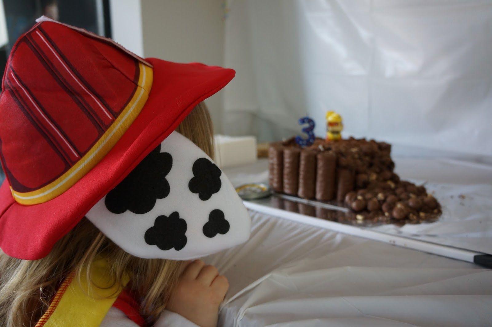 toddler in marshall costume looking at paw patrol cake