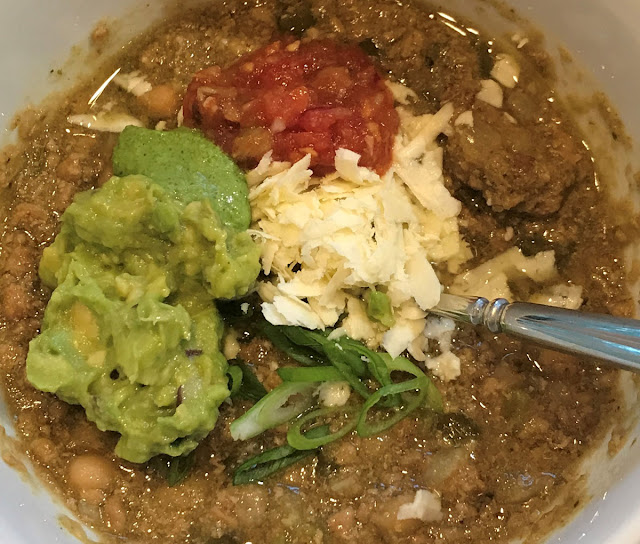 white bowl with green pork chili, guacamole, cilantro jalapeno sauce, salsa, grated feta, and sliced scallions