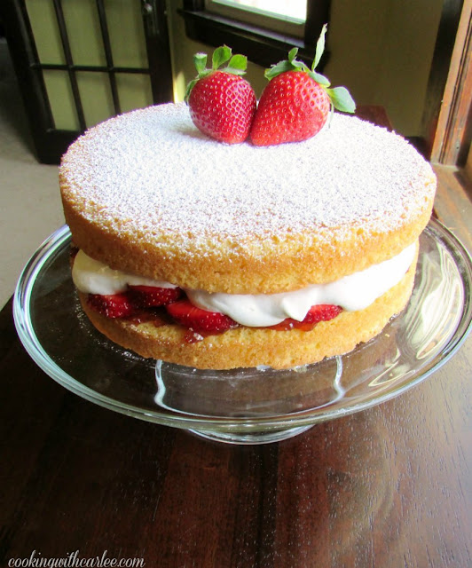 whole victoria sponge cake with strawberries and whipped cream filling