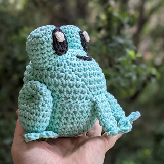 A white hand holding up a crochet frog made with pastel green cotton yarn.