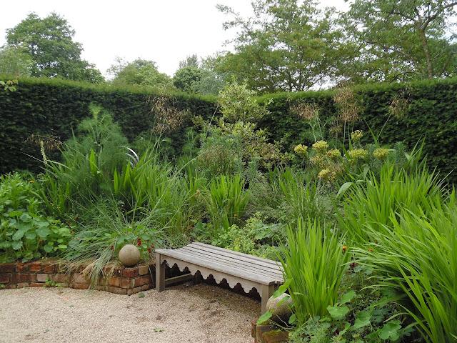 ceglany murek cegła w ogrodzie drewniana ławka
