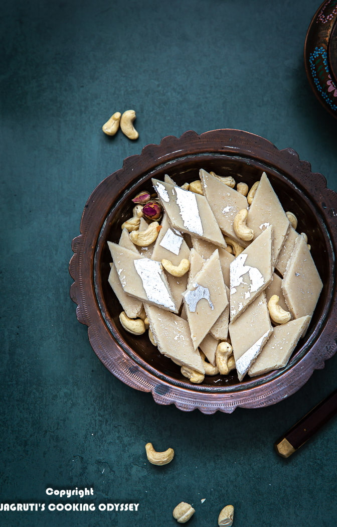Kaju katli arranged in a bowl with some cashews and dried rose petals on the side